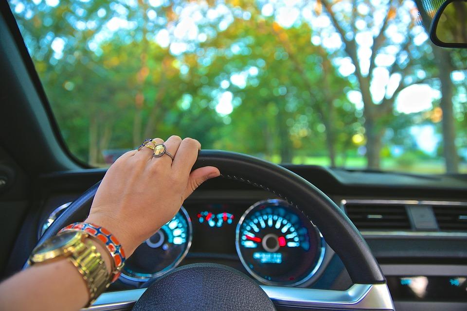 Mujer conduciendo vehículo en autoescuela.